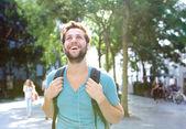 Pohledný mladý muž chodit venku s batohem