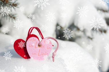 red hearts toy in snowfall on fir tree