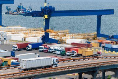 Truck carries container to warehouse near sea