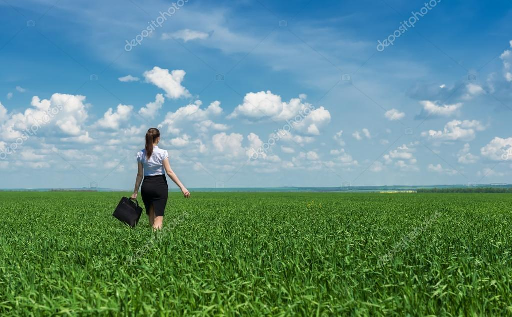 girl with a briefcase walking on grass