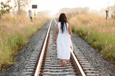 Young woman walking down a railway track