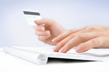 Woman's hands holding a credit card and using computer keyboard for online shopping