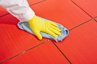 Hand with yellow gloves and blue towel clean red tiles grout