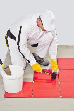 Worker Applies with Rubber Hummer Red Tile on a Floor