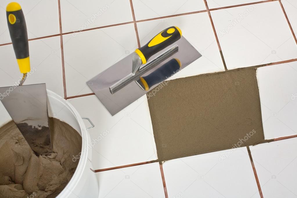 Riparato il vecchio pavimento di piastrelle bianche con adesivo di