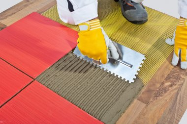worker apply ceramic tiles on wooden floor mesh trowel