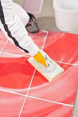 worker clean with sponge trowel tile joints grout