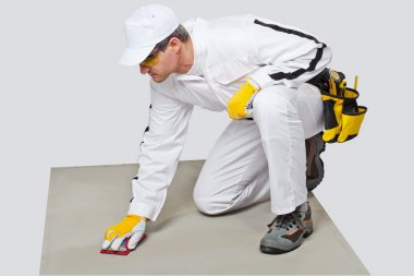 worker sand paper clean cement substrate