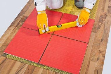 Worker levels Tiles applied on old wooden Floor reinforced net