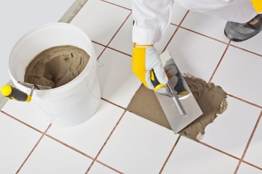 Worker with trowel repairs old white tiles with tile adhesive