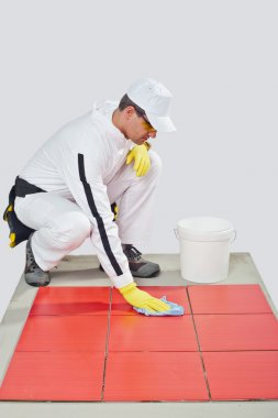 Worker with yellow gloves and blue towel clean red tiles
