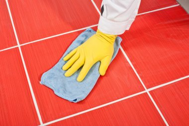 Worker with yellow gloves and blue towel clean red tiles grout