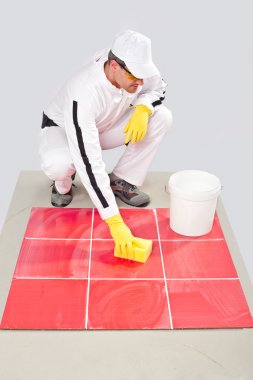 Worker with yellow gloves and yellow sponge clean tiles
