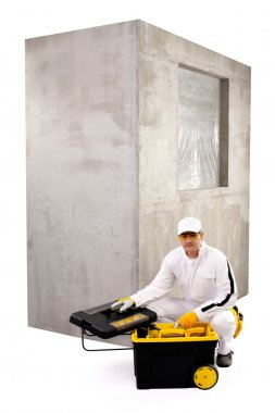 Construction worker with open toolbox and cement wall on white b
