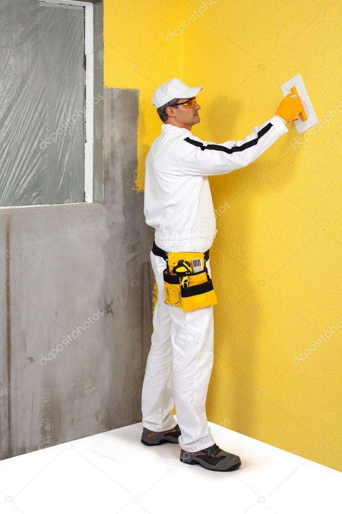 Worker spreading a plaster on a wall