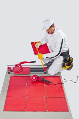 Construction worker cutting ceramic tiles