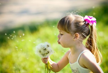 Little girl closeup portrait with dandelion