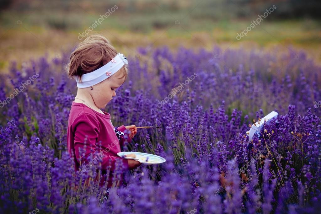 Girl draws a picture in a lavandovy field