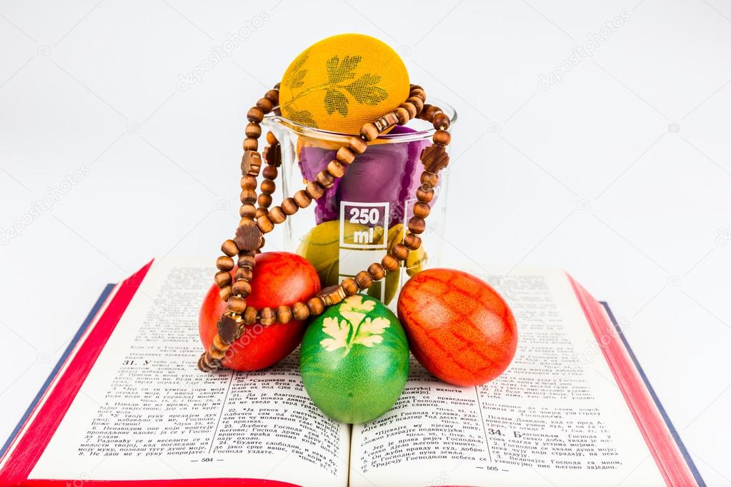 Easter eggs in lab glass with rosary on a holy Bible