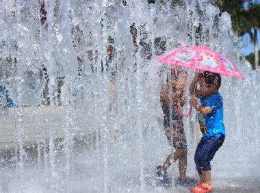 Kids running playing in water fountains