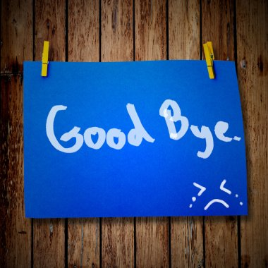 Good bye note paper and clothes peg on a wooden background with