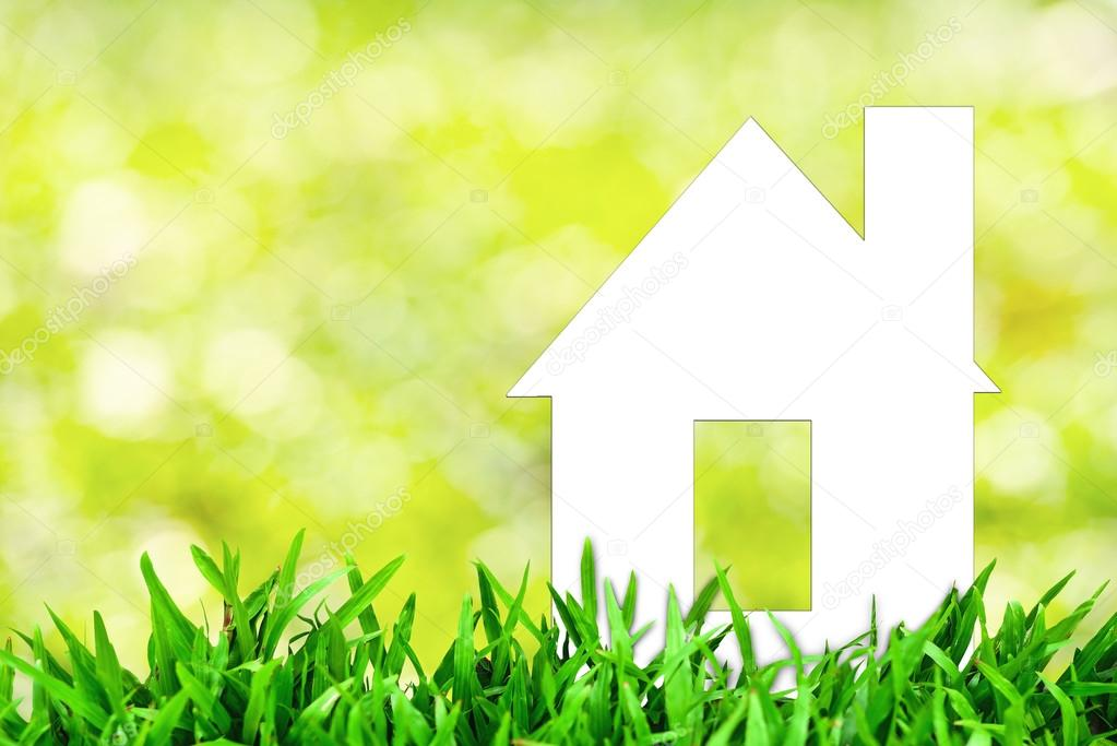 White paper house and spring green grass with green bokeh