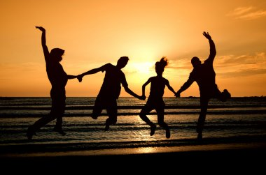 Group of happy parting on the beach at sunrise