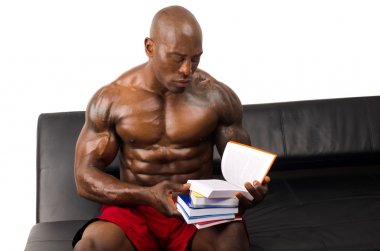 Bodybuilder training hard while reading a book