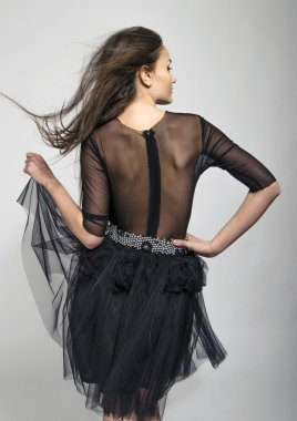 Girl posing fashion from the back wearing a lace black dress. Young woman with see through dress on the back
