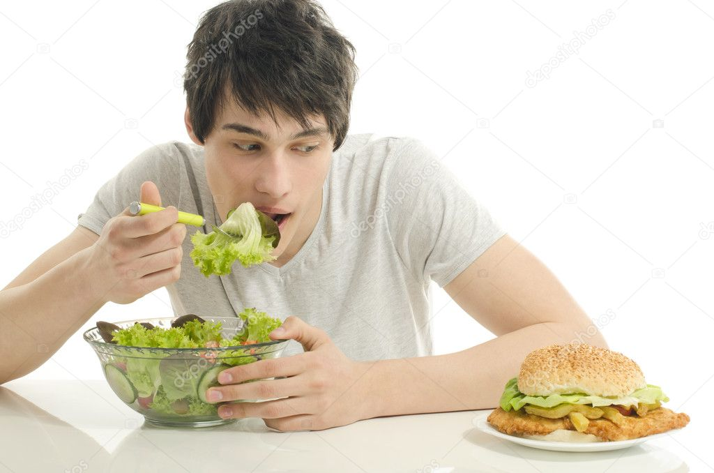 Man offering you a salad and a hamburger. Young man holding in front a bowl of salad and a big burger. Choosing between good healthy food and bad unhealthy food