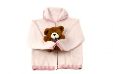 Close up of a baby pink blouse and a brown teddy bear isolated