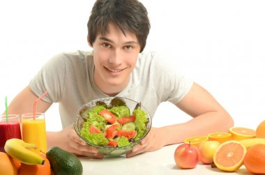 Happy man having a table full of organic food,juices and smoothie. Cheerful young man eating healthy salad and fruits. Isolated on white.