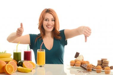Woman choosing between fruits, smoothie and organic healthy food against sweets, sugar, lots of candies, unhealthy food