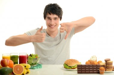Man choosing between fruits, smoothie and organic healthy food against sweets, sugar, lots of candies and a big hamburger, unhealthy food