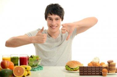 Man choosing between fruits, smoothie and organic healthy food against sweets, sugar, lots of candies and a big hamburger, unhealthy food