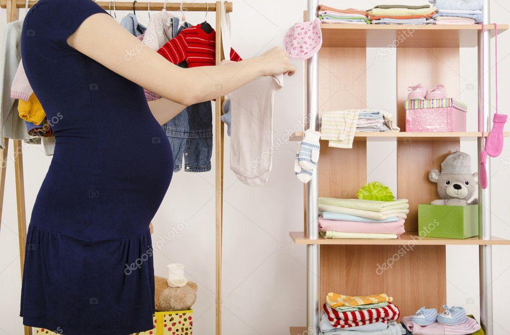 mujer embarazada comprando ropa para su beb recin nacido vestir armario con ropa dispuesta en armario del recin nacido nios