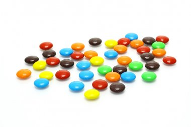 Lots of colorful candies spread on white background
