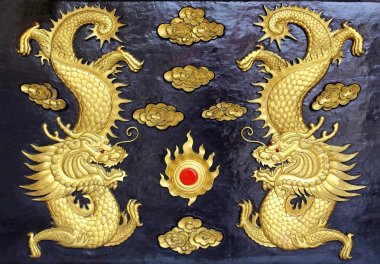 Two golden dragons (Chinese: Long) wood carving in black backgro