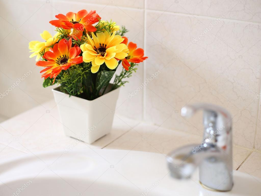 artificial flowers at wash basin in a bathroom stock