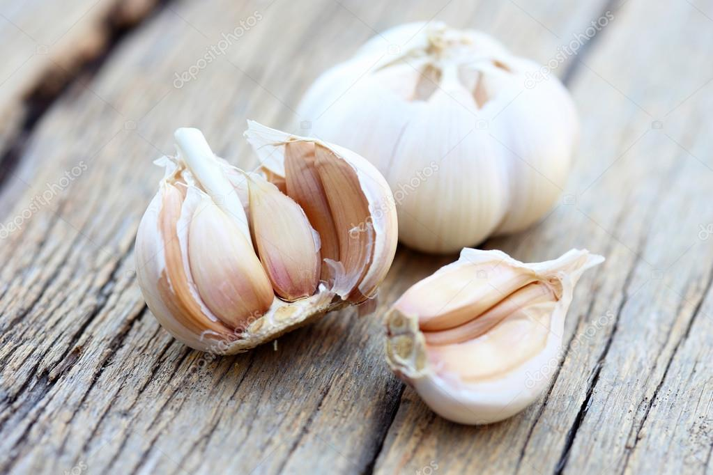 Organic garlic on wood background