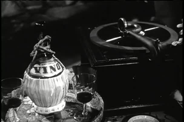 gramofon vedle zásobníku s láhví vína a brýle