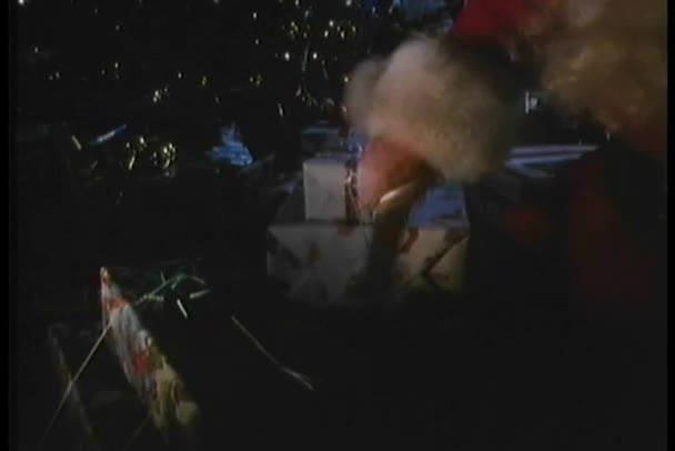 Santa Claus, hogy bemutatja a karácsonyfa alatt