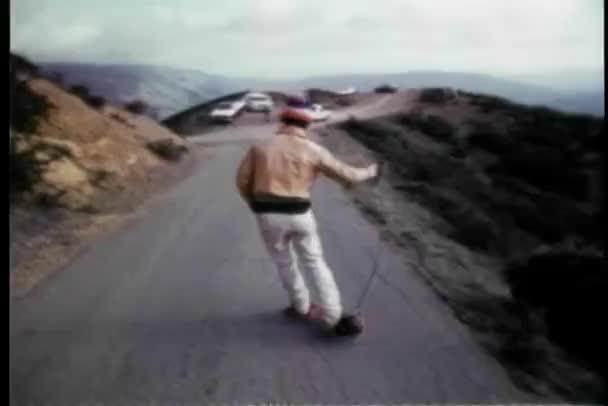 zadní pohled na člověka, skateboarding na horské cestě