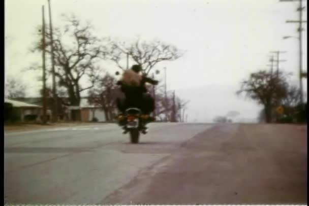 zadní pohled na muže a žena na koni motocyklu na venkovské silnici