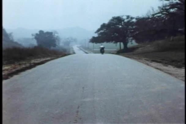 zadní pohled na motocyklu policejní honička na venkovské silnici