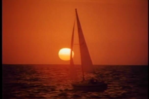 Nyugodt jelenet vitorlás a tengeren sodródó naplementekor