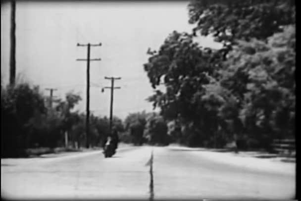 policista na motorce honí auto