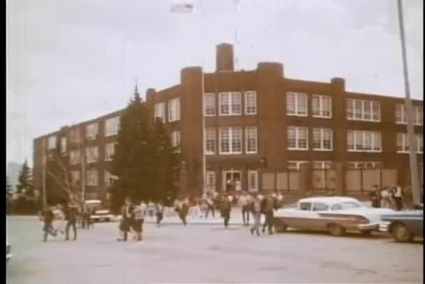 Wide shot of high school students leaving school