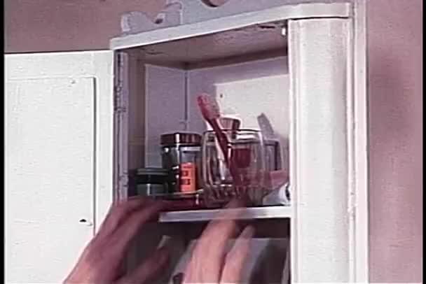 Medium shot der Hände tastend für Zahnbürste im Badezimmerschrank