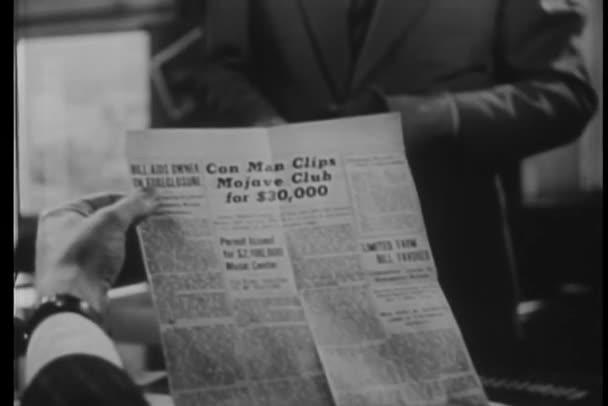 Ruka držící výstřižek z novin